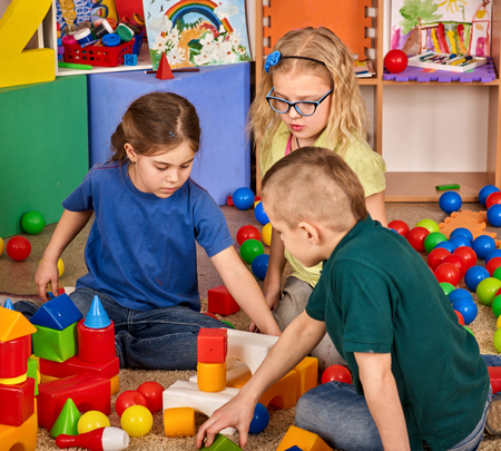 Children building blocks in kindergarten. Group kids playing toy on floor. Interior preschool. Kid is keen on playing dice. Game of block replaces games on smartphone.