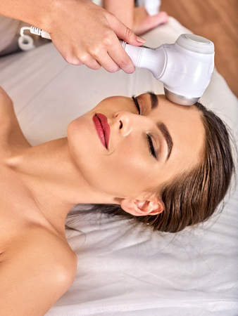 Ultrasonic facial treatment on ultrasound face machine. Woman receiving electric lift massage at spa salon. Electronic stimulation female muscles microcurrent therapy. She watches her face.