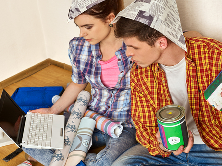 Repair family couple building home using laptop. Woman and man in newspaper cap renovation apartment. Purchase furniture through Internet. Online shop for repair. Modern technologies in everyday life. Stock Photo