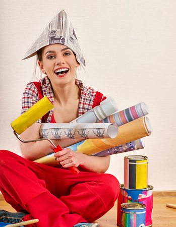 Repair home woman holding paint roller for wallpaper. Aggressive screaming girl in newspaper cap renovation apartment on isolated. Loan for housing for students. Woman likes repair apartment. Stock Photo