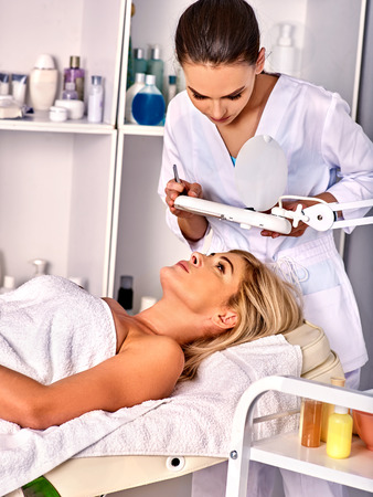Eyebrow treatment of woman middle-aged in spa salon. Tweezing eyebrow by beautician. 40s old female under cosmetic lamp.