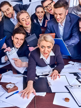 Mad business people office. Team people are unhappy with their leader. Intern woman manager does not cope with his duties. Persecution of a new employee of firm. Documents for signature.