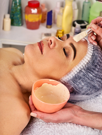 Collagen facial mask for skin treatment. Face of woman of elderly woman 50-60 years old receiving cosmetic procedure in beauty salon close up . Treatment by professional beautician .