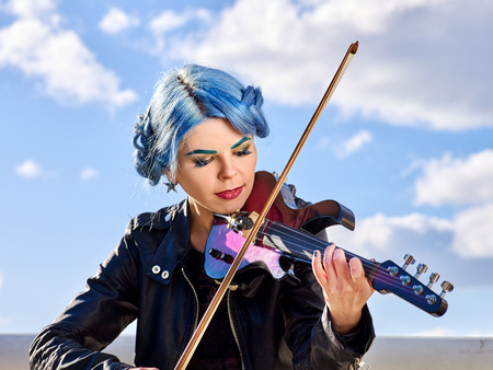 Playing viola woman perform music on violin in park outdoor. Girl with blue hairstyle and eyebrows performing jazz on city street. Music festival on street in a bright sunny day. Spring inspiration. Archivio Fotografico