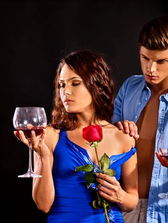 Le coppie bevono insieme il vetro del vino rosso. Fiore rosa della stretta della donna L'uomo spoglia la sua amata donna. Relazioni senza obblighi. Conoscenza in un night club.