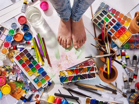 Authentic paint brushes still life on floor in art class school. Group of brush in clay jar. Barefooted female feet among creative mess. Stockfoto
