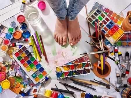 Authentisches Pinselstillleben auf Boden in der Kunstunterrichtsschule. Gruppe der Bürste im Lehmglas. Barfüßig weibliche Füße unter kreativer Verwirrung.