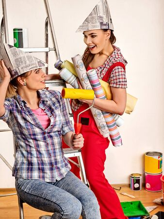 Repair home women holding painting tools roller for wallpaper. Happy girls wearing newspaper hat renovation apartment in room. Sisters install a stepladder.