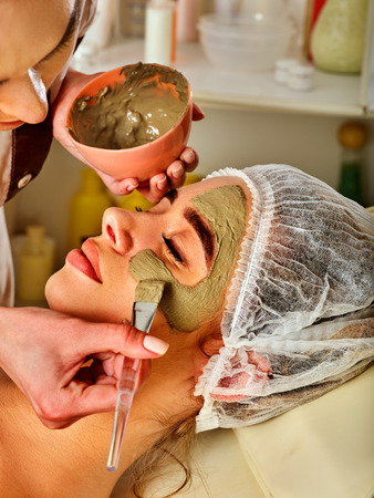 Mud facial mask of woman in spa salon. Massage with clay full face. Beautician with brush therapeutic procedure background. Healing clay to preserve youth. Stock Photo