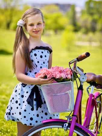 Bicycle girl with flowers in spring park. Child girl wearing white polka dots dress rides bicycle with pink flowers basket. Green and blu sky on background.