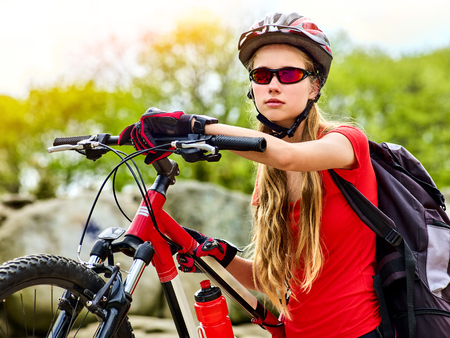 Woman on bicycle ride mountain. Girl with smart watch traveling in summer park. Cycling person with rucksack counts pulse after sport training.