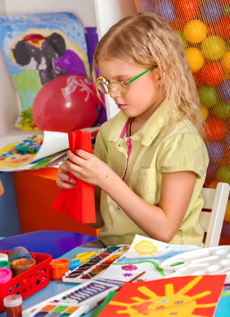 Child cutting paper in class. Kids development and social lerning children in school. Childrens origami project with teacher in kindergarten. Preparation for origami exhibition. Stock Photo
