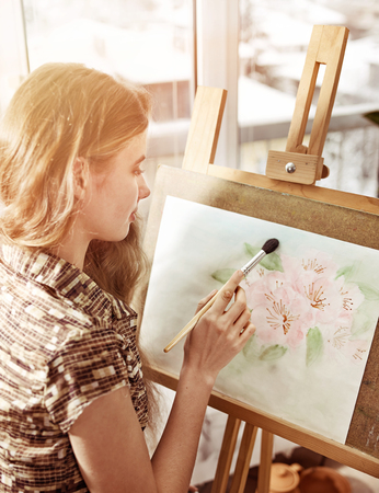 Artist painting on easel in studio. Authentic girl paints with brush in morning sunlight dawn light toning. Private business in drawing. Relaxation and solution of psychological problems.