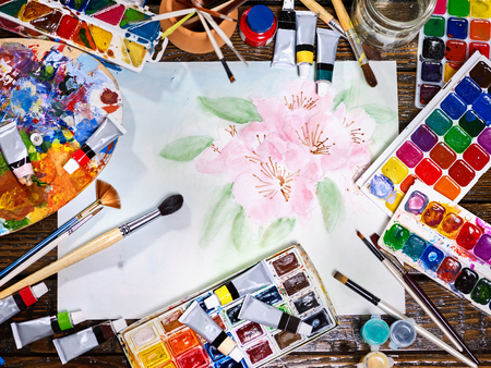 Authentic paint brushes still life in art class school. Group of brush in clay jar. Bouquet of tulip flowers as symbol of spring discounts. Copy space for text. Courses on drawing for children. Banque d'images