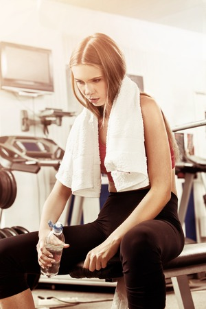Woman in gym workout with fitness equipment. Girl drink from bottle water relaxing after workout at gym. Female tired after training. She has sport towel around his neck. Warm-glow sepia toning.