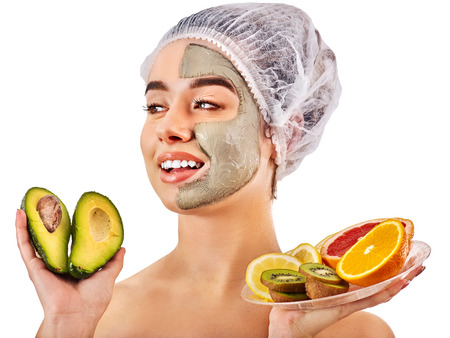 Avocado clay face mask. Woman in medical hat holding half of green fruit isolated background. Facial beautiful procedure concept. Masks for skin created from natural ingredient. Acne Removal. Stock Photo