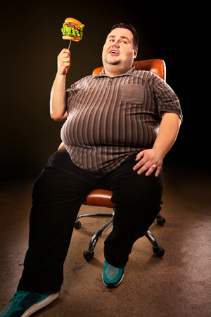 Diet failure of fat man eating fast food hamberger. Happy smile overweight person who spoiled healthy food by eating huge hamburger on fork. Person is happy that he defeated anorexia.