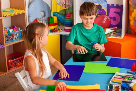 Escolares con tijeras en manos de los niños cortando papel con el maestro en la sala de clase. Proyecto infantil en jardín de infantes. Grupo grande de niñas y niños juntos. Exposición de origami. Foto de archivo