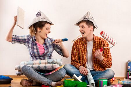 Repair family by happy couple building home using spirit level to measure. Woman and man in newspaper cap renovation apartment. Loan for housing for family.