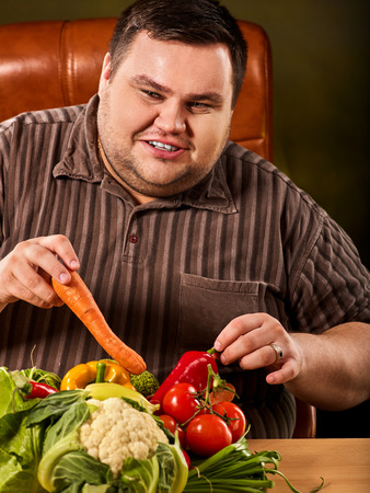 Diet fat man eating healthy food with vegetables cauliflower and sweet pepper with radish, tomatoes for overweight male. Male trying to lose weight first time. Hungry person ready to eat everything. Recovery.