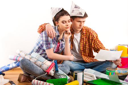 Repair family by happy couple building home using white laptop. Woman and man in newspaper cap renovation apartment. Loan for housing for a couple. They ask friends to help with repairs.