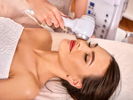 Ultrasonic facial treatment on ultrasound face machine. Woman receiving electric lift massage at spa salon. Electronic stimulation female muscles. Professional equipment microcurrent therapy. Recovery Stock Photo