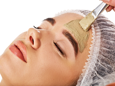 Mud facial mask of woman in spa salon. Massage with clay full face. Girl on with therapy room. Beautician with brush therapeutic procedure isolated background. Healing clay for face. Facelift.