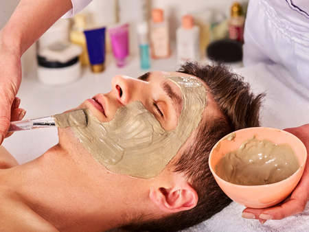 Mud facial mask of man in spa salon. Cleansing massage with clay full face. Lying man on therapy room for skin detox. Beautician with bowl therapeutic procedure. Anti-aging cosmetic mask. Foto de archivo