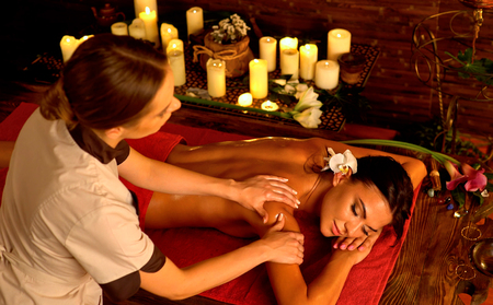 Deep tissue massage treatment in Ayurveda of woman in spa salon. Girl on candles background treats problem back. Luxary Filipino therapy interior with working masseuse.