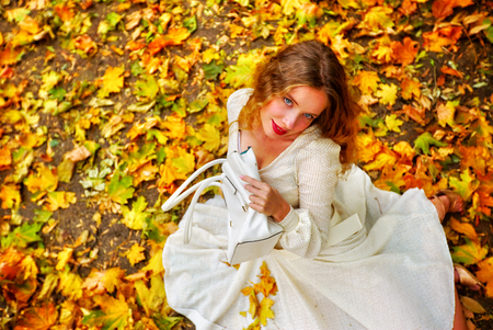 Autumn fashion feminity lace dress with long sleeve in princess style. Top view of girl model with a look of coquetry sitting on color foliage bouquet sitting on fall leaves in city park outdoor.