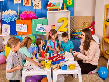 Kleine Schüler mit Lehrermalerei in der Kunstschulklasse. Kinderzeichnung durch Farben. Die handwerkliche Zeichenausbildung entwickelt die kreativen Fähigkeiten der Kinder. Kunstschule für Kinder.