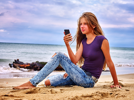 Teenager girl sitting on sand near sea call help by phone. Summer girl sea back on water. Nature beauty. Stock Photo