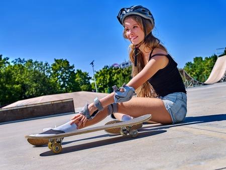 Sportmädchen mit Verletzung, die nahe ihrem Skateboard sitzt und Knöchel im Freien berührt.