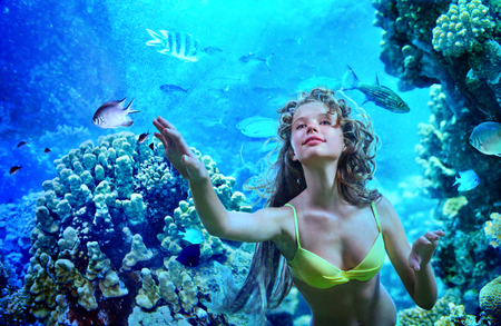 Girl is diving under water  amoung coral fish. 免版税图像