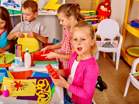 Group children holding colored paper on table in kindergarten . Child development. Stock Photo