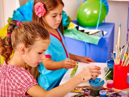 Las niñas siguen pintando con pincel sobre la mesa en el jardín de infancia. Aprendizaje de pintura.