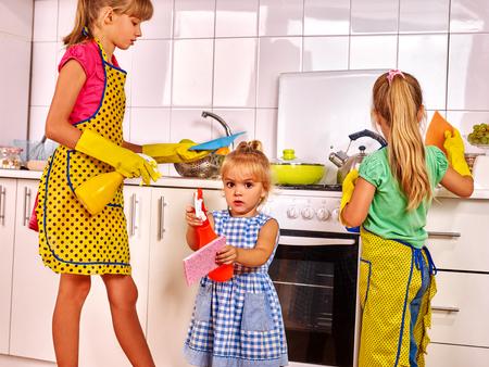 Children little girl wash kitchen at kitchen. Kitchen cleaners. Banque d'images
