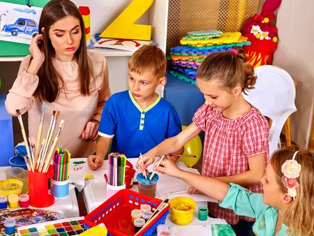 Niños con maestra mujer pintando sobre papel en la mesa en la escuela de jardín de infantes. Escuela de pintura.