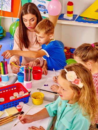 Enfants avec une femme enseignante peignant sur papier à table à la maternelle. Ecole de peinture.