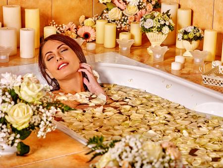 Woman relaxing at flower water spa. Luxury bathroom in spa salon.
