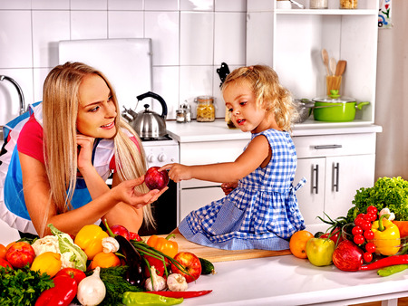 Mother and daughter spend time at kitchen.