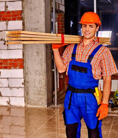 Happy man in builder uniform carry wooden boards indoor.