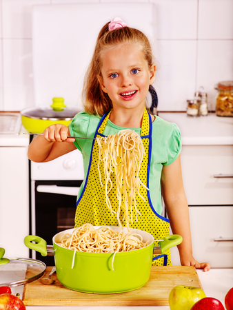 Children eating spaghetti from pan at kitchen.