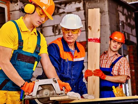 Gente felice del gruppo di tre persone builder con sega circolare.