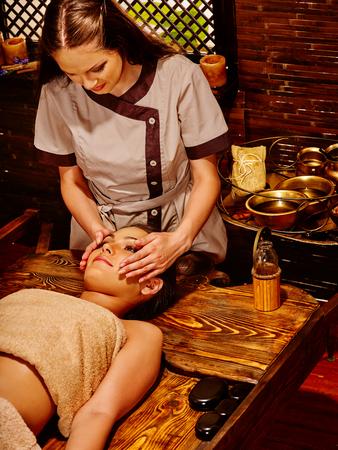 Couple having oil facial spa treatment in woden salon.