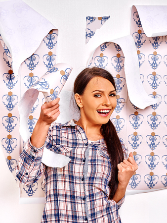 Pretty woman glues wallpaper at home.