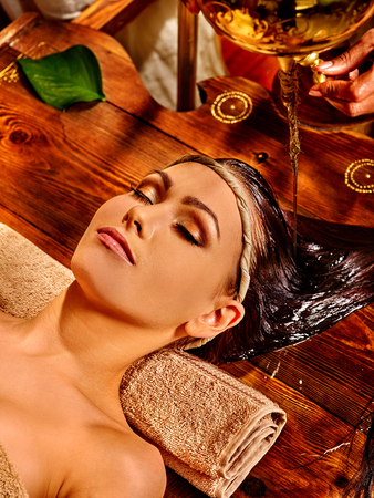 Young woman lying on back having oil Ayurveda spa treatment. Stock Photo