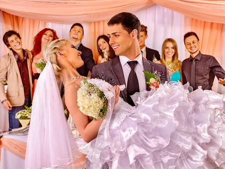 Groom  carries bride on his hands  at wedding.