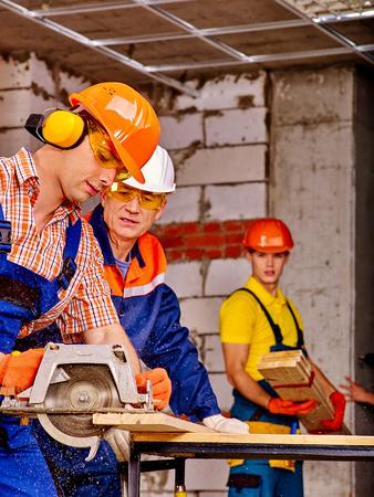 Happy group people builder with circular saw working indoor. Reklamní fotografie