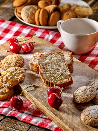 Oatmeal cookies and cherry on kitchen cutting board gingham checkered cotton fabric on table in village style for picnic with plate of macaron background.
